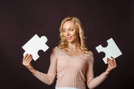 Photo for Happy blonde woman holding jigsaw pieces isolated on black - Royalty Free Image