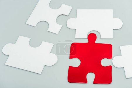 red and white jigsaw pieces isolated on grey