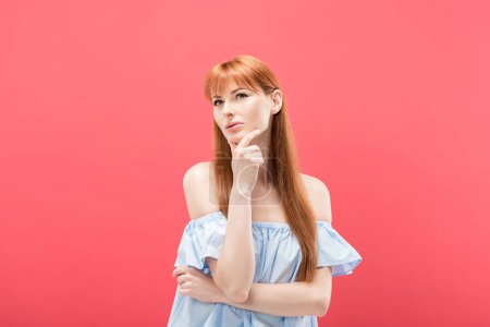 Photo for Pensive redhead woman touching chin and looking away isolated on pink - Royalty Free Image