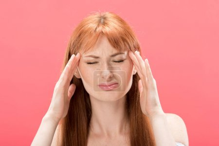 Photo for Front view of redhead young woman with headache touching head isolated on pink - Royalty Free Image