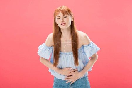 Photo pour Rousse femme avec maux d'estomac toucher le ventre avec les yeux fermés isolé sur rose - image libre de droit