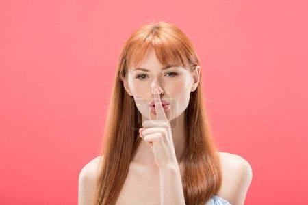 Photo pour Vue avant de la fille rousse regardant l'appareil-photo et affichant le geste secret d'isolement sur le rose - image libre de droit