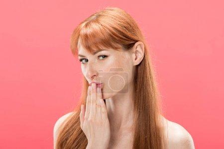 Photo pour Rousse nue fille toucher les lèvres avec les doigts et regarder la caméra isolée sur rose - image libre de droit