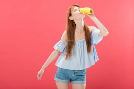 Photo pour Attrayant rousse fille en jeans shorts boisson avec les yeux fermés isolé sur rose - image libre de droit