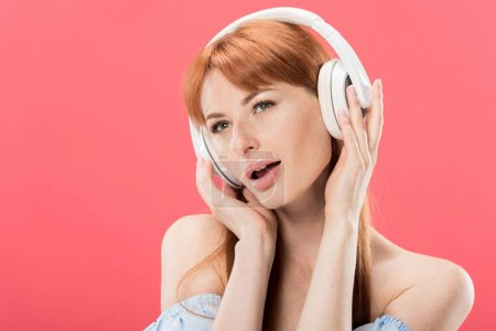 Photo for Attractive redhead woman listening music in headphones and looking away isolated on pink - Royalty Free Image
