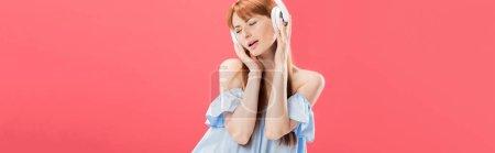 Photo pour Tir panoramique de la femme rousse attirante écoutant la musique dans le casque avec les yeux fermés isolés sur le rose - image libre de droit