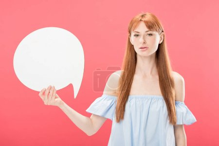 Photo for Serious attractive redhead girl holding blank speech bubble and looking at camera isolated on pink - Royalty Free Image