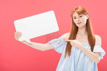 Photo pour Jeune femme rousse pointant avec le doigt à la bulle vide de discours et regardant la caméra d'isolement sur le rose - image libre de droit
