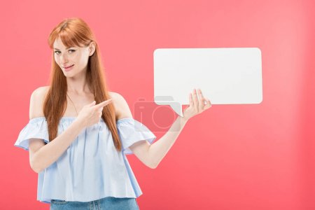 Photo for Redhead young woman pointing with finger at empty speech bubble and looking at camera isolated on pink - Royalty Free Image