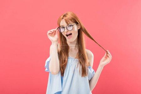 Foto de Niña pelirroja sonriente en gafas y blusa elegante jugando con el pelo y mirando la cámara aislada en rosa - Imagen libre de derechos