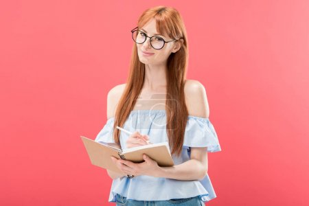 Photo for Attractive redhead woman in glasses holding pencil and textbook isolated on pink - Royalty Free Image