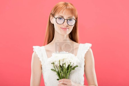Photo for Front view of attractive redhead girl in glasses and white dress holding flowers and smiling isolated on pink - Royalty Free Image