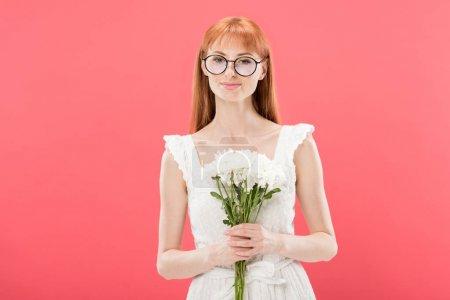 Photo pour Vue avant de la fille attirante de rousse dans des glaces et des fleurs blanches de fixation de robe et souriant d'isolement sur le rose - image libre de droit