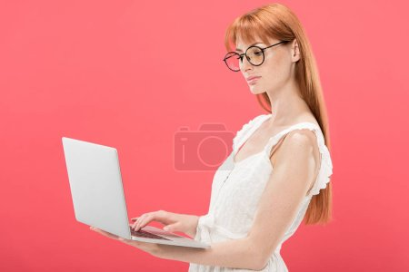 Photo for Serious redhead young woman in glasses using laptop isolated on pink - Royalty Free Image