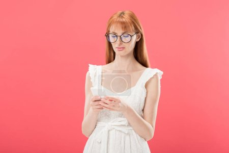 Photo for Redhead woman in glasses and white dress using smartphone isolated on pink - Royalty Free Image