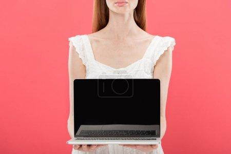 abgeschnittene Ansicht der rothaarigen jungen Frau in Brille mit Laptop und leerem Bildschirm isoliert auf rosa