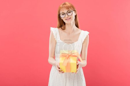Photo for Front view of smiling redhead girl in glasses and white dress holding birthday present and looking at camera isolated on pink - Royalty Free Image