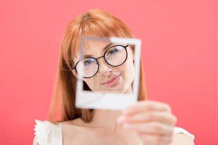 Photo pour Kiev, Ukraine - 23 mai 2019: focus sélectif de la fille rousse attrayante dans les lunettes tenant le cadre d'appareil photo vintage isolé sur le rose - image libre de droit