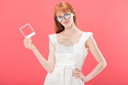 Photo for Pretty redhead young woman in glasses and white dress holding vintage camera frame and looking at camera isolated on pink - Royalty Free Image