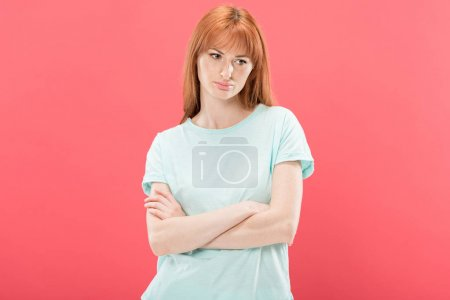 Photo for Front view of pensive redhead young woman in t-shirt standing with crossed arms and looking away isolated on pink - Royalty Free Image