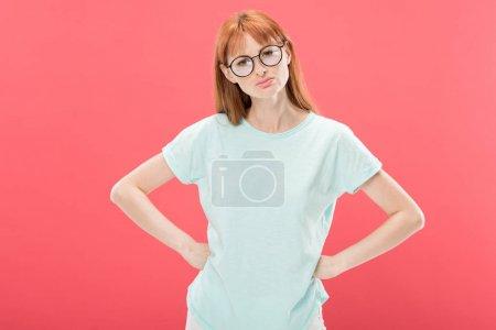 Photo pour Vue de face de curieuse rousse femme à lunettes avec les mains sur les hanches en regardant la caméra isolée sur rose - image libre de droit