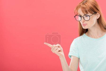 Photo pour Chère rousse femme en t-shirt pointant avec doigt isolé sur rose - image libre de droit