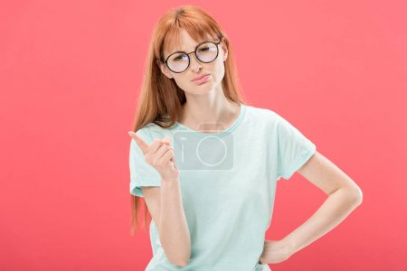 Photo for Front view of serious redhead woman in glasses and t-shirt standing with hand on hip and shaking finger isolated on pink - Royalty Free Image