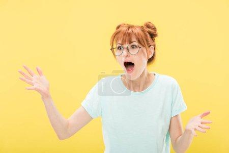 Photo pour Rousse choquée fille dans des lunettes agitant les mains avec la bouche ouverte isolé sur jaune - image libre de droit