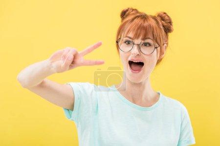 Photo pour Fille excitée de rousse dans des glaces et le t-shirt affichant le signe de paix d'isolement sur le jaune - image libre de droit