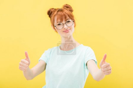 Photo for Front view of smiling redhead girl in glasses showing thumbs up and looking at camera isolated on yellow - Royalty Free Image