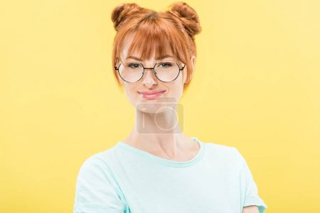 Photo for Front view of smiling redhead girl in glasses and t-shirt looking at camera isolated on yellow - Royalty Free Image