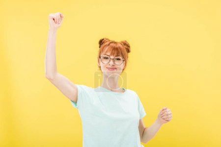 Photo for Pleased redhead girl in glasses and t-shirt gesturing isolated on yellow - Royalty Free Image