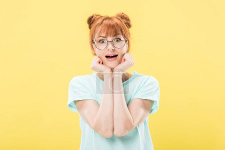 Photo for Front view of surprised redhead girl in glasses propping face with hands and looking at camera isolated on yellow - Royalty Free Image