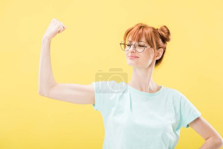 Photo pour Confiant heureux rousse fille en lunettes et t-shirt tenant poing vers le haut isolé sur jaune - image libre de droit