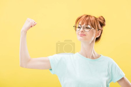 Photo for Confident pleased redhead girl in glasses and t-shirt holding fist up isolated on yellow - Royalty Free Image