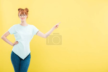 Photo for Smiling redhead girl in glasses standing with hand on hip and pointing with finger isolated on yellow - Royalty Free Image