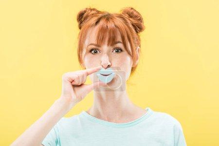 Photo pour Vue de face de rousse fille tenant des lèvres en papier et regardant la caméra isolée sur jaune - image libre de droit