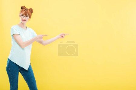 Photo pour Souriant rousse fille en lunettes et t-shirt pointant avec les doigts et regardant la caméra isolée sur jaune - image libre de droit