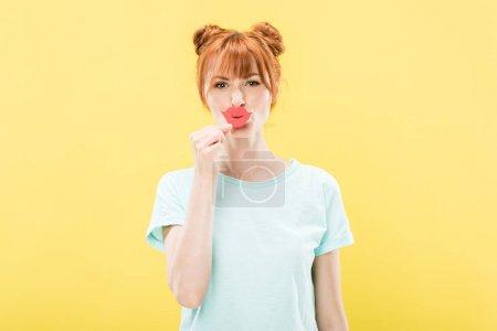 Photo pour Vue de face de la fille rousse en t-shirt tenant lèvres en papier et regardant la caméra isolée sur jaune - image libre de droit