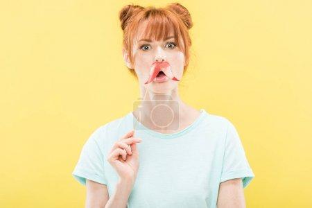 Photo pour Vue de face de surprise rousse fille en t-shirt tenant jouet moustache - image libre de droit