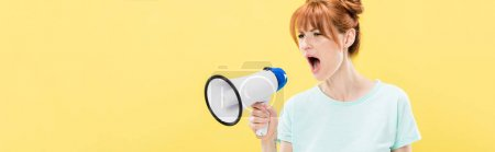 Photo for Panoramic shot of angry redhead young woman holding megaphone and screaming isolated on yellow - Royalty Free Image