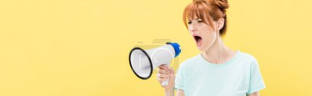 Photo pour Plan panoramique de rousse en colère jeune femme tenant mégaphone et criant isolé sur jaune - image libre de droit