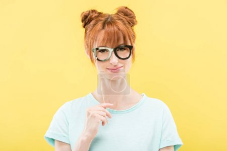 Photo for Front view of smiling redhead girl in t-shirt holding toy glasses and looking at camera isolated on yellow - Royalty Free Image