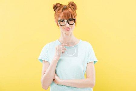 Foto de Vista frontal de la chica pelirroja sonriente en la camiseta sosteniendo gafas de juguete y mirando la cámara aislada en amarillo - Imagen libre de derechos