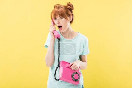 Photo for Shocked redhead young woman talking on retro telephone isolated on yellow - Royalty Free Image