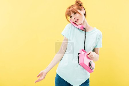 attractive redhead young woman talking on retro telephone isolated on yellow