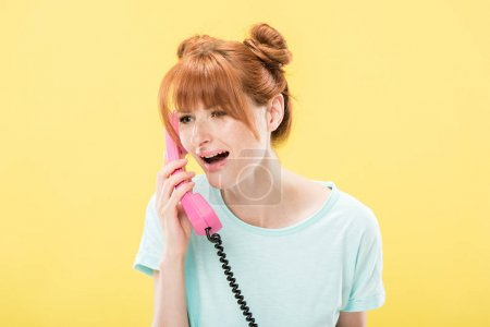 upset redhead young woman talking on retro telephone isolated on yellow