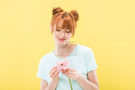 Photo pour Vue avant de la jeune femme de rousse de sourire dans la fleur de fixation de t-shirt d'isolement sur le jaune - image libre de droit