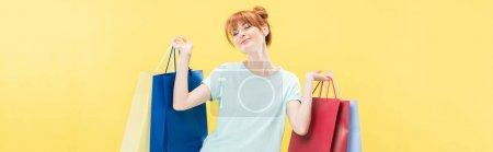 Photo pour Plan panoramique de fille rousse souriante tenant sac à provisions isolé sur jaune - image libre de droit