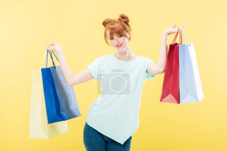 smiling redhead girl holding shopping bags and looking at camera isolated on yellow